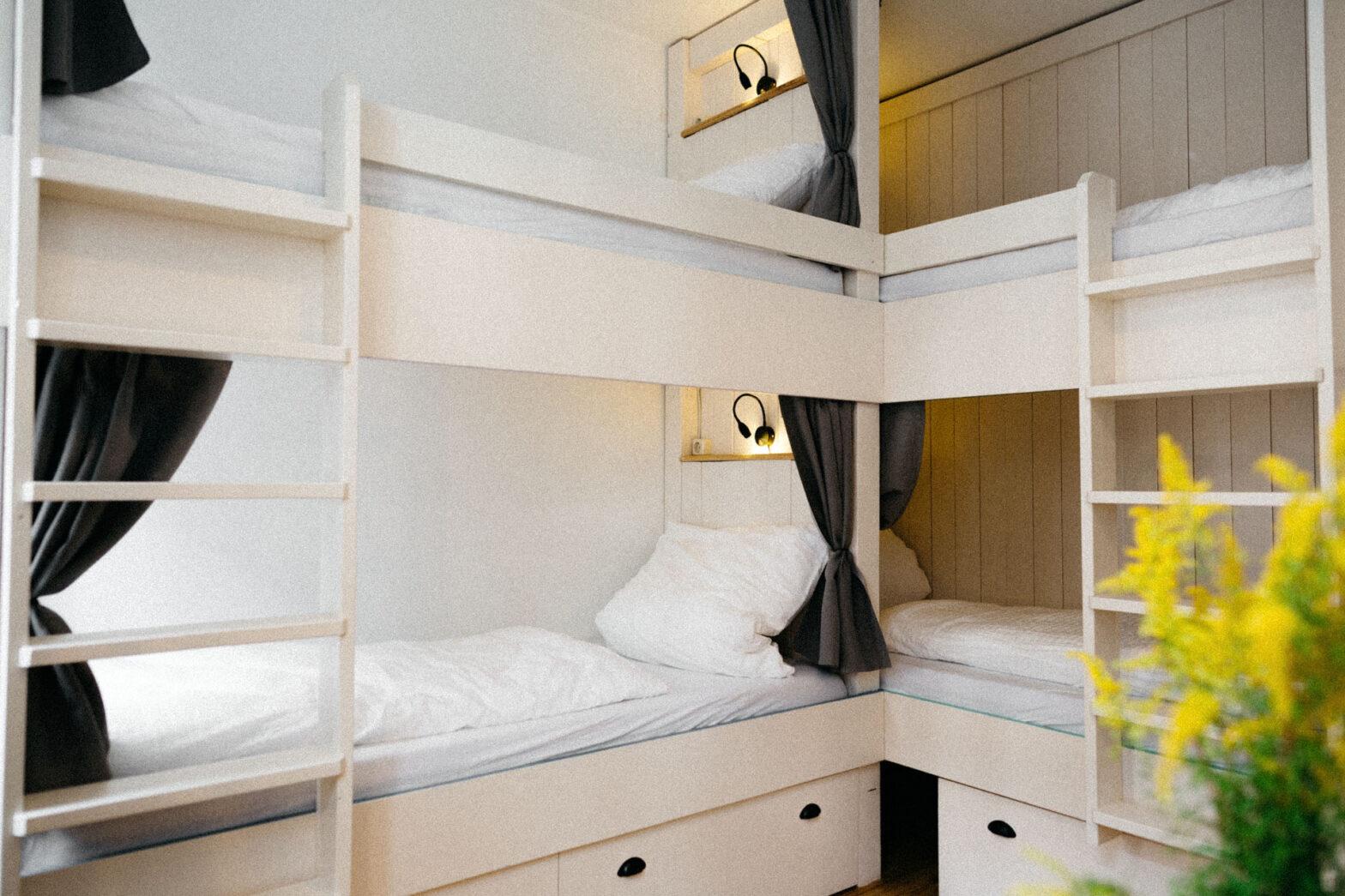 Zwei schöne weiße Hochbetten um die Ecke des Raumes mit schwarzen Vorhängen an den Etagen der Betten und einer schönen pflanze im Vordergrund