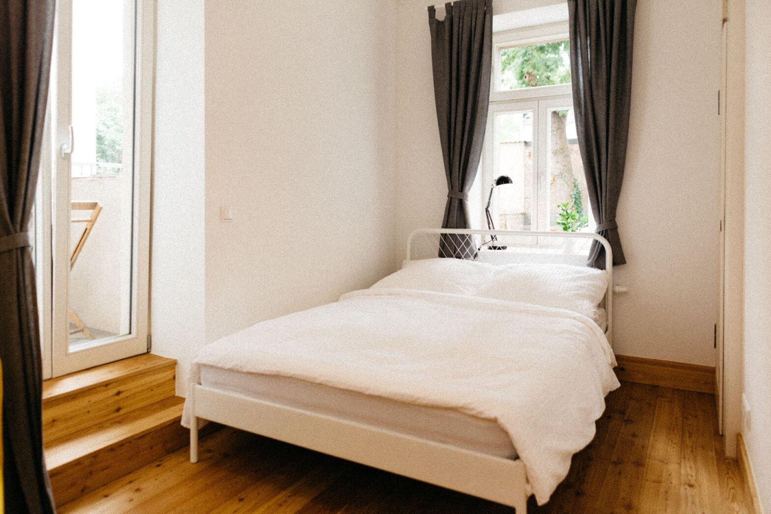 ein Einzelzimmer mit weißem schicken Bett und schwarzen Vorhängen. Sehr schöner Holzboden und eine Treppe zum Balkon.