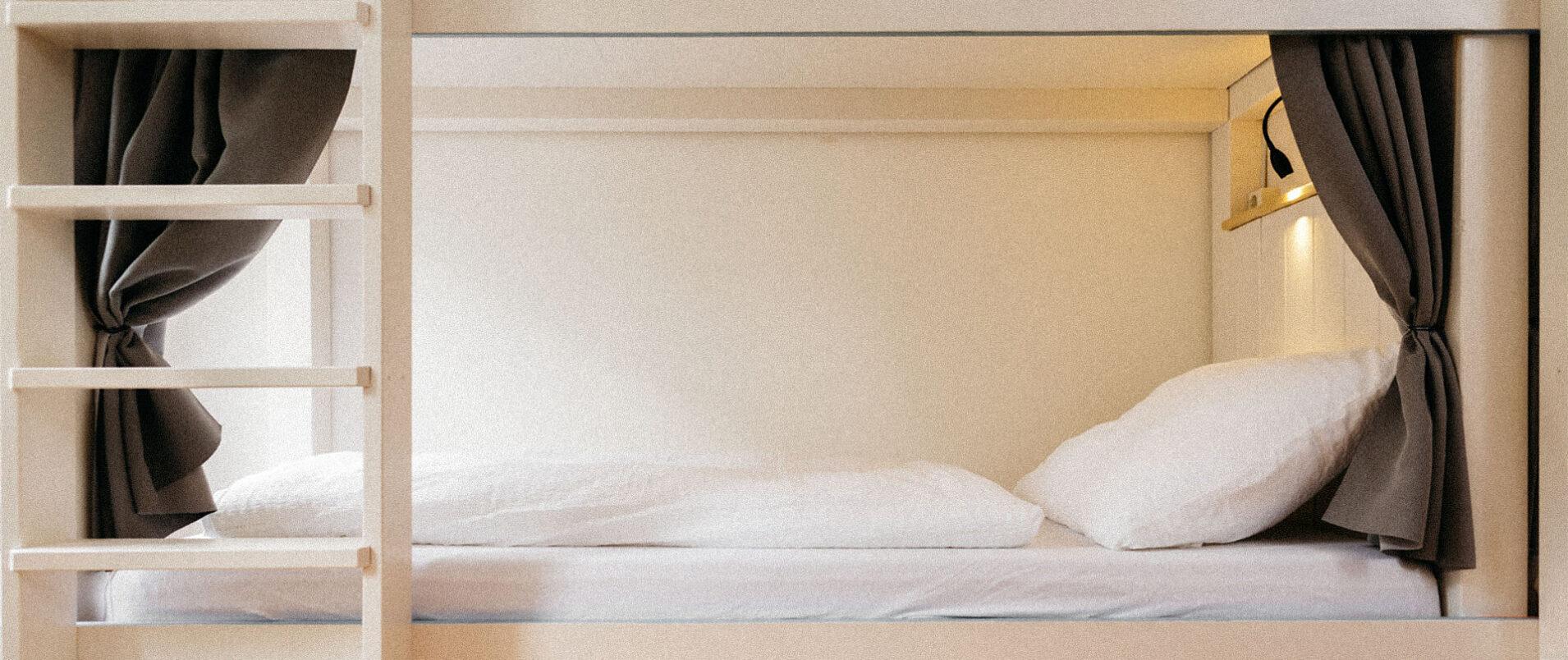 Hochbett von der Seite fotografiert mit schwarzen Vorhängen und weißer Bettwäsche