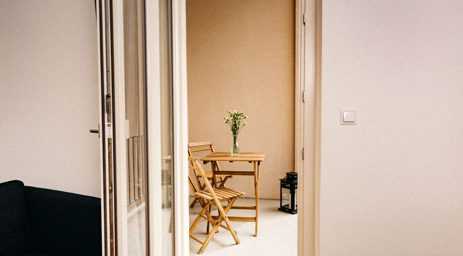 Blick durch eine helle Tür auf eine strahlende Küche mit gemütlichen Tisch und Stühlen aus Holz