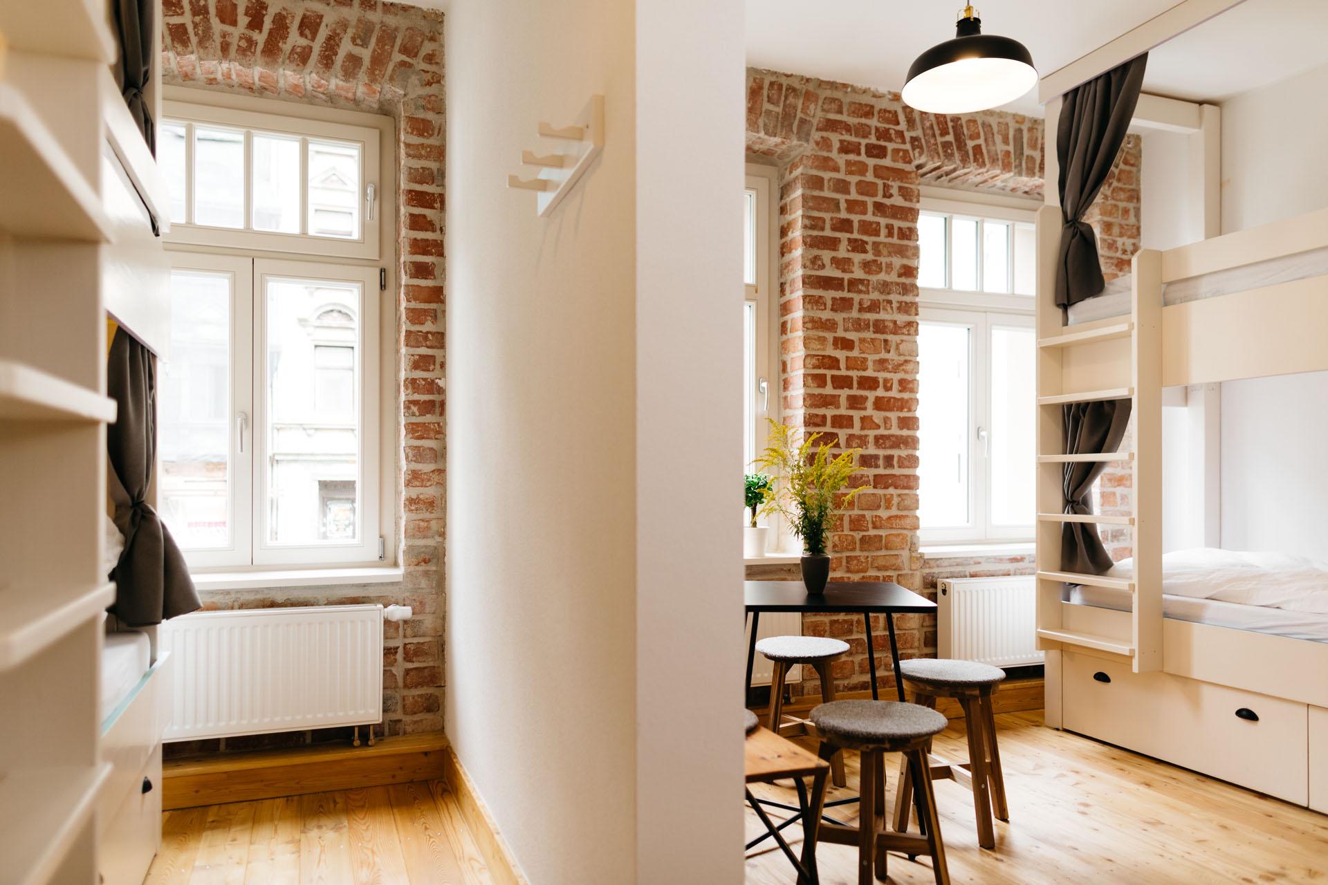 Blick auf ein großes 10er Zimmer mit den Doppelbetten links und rechts im Bild an den Wänden und einer Trennwand neben der Tisch und Stühle stehen.