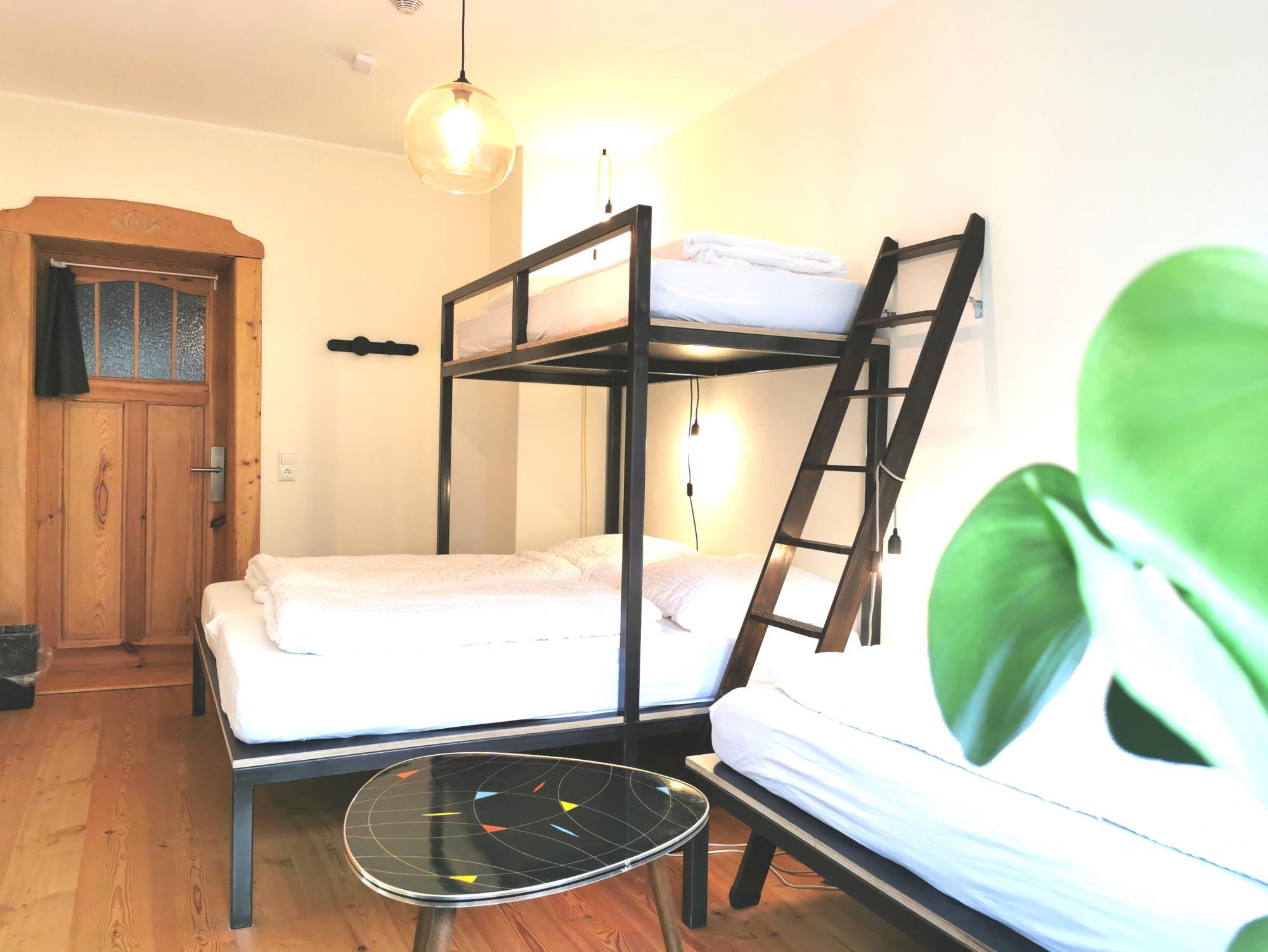 Blick auf eines der neuen versetzten Doppelbetten mit Hochbett in einem der privaten 4er Zimmer