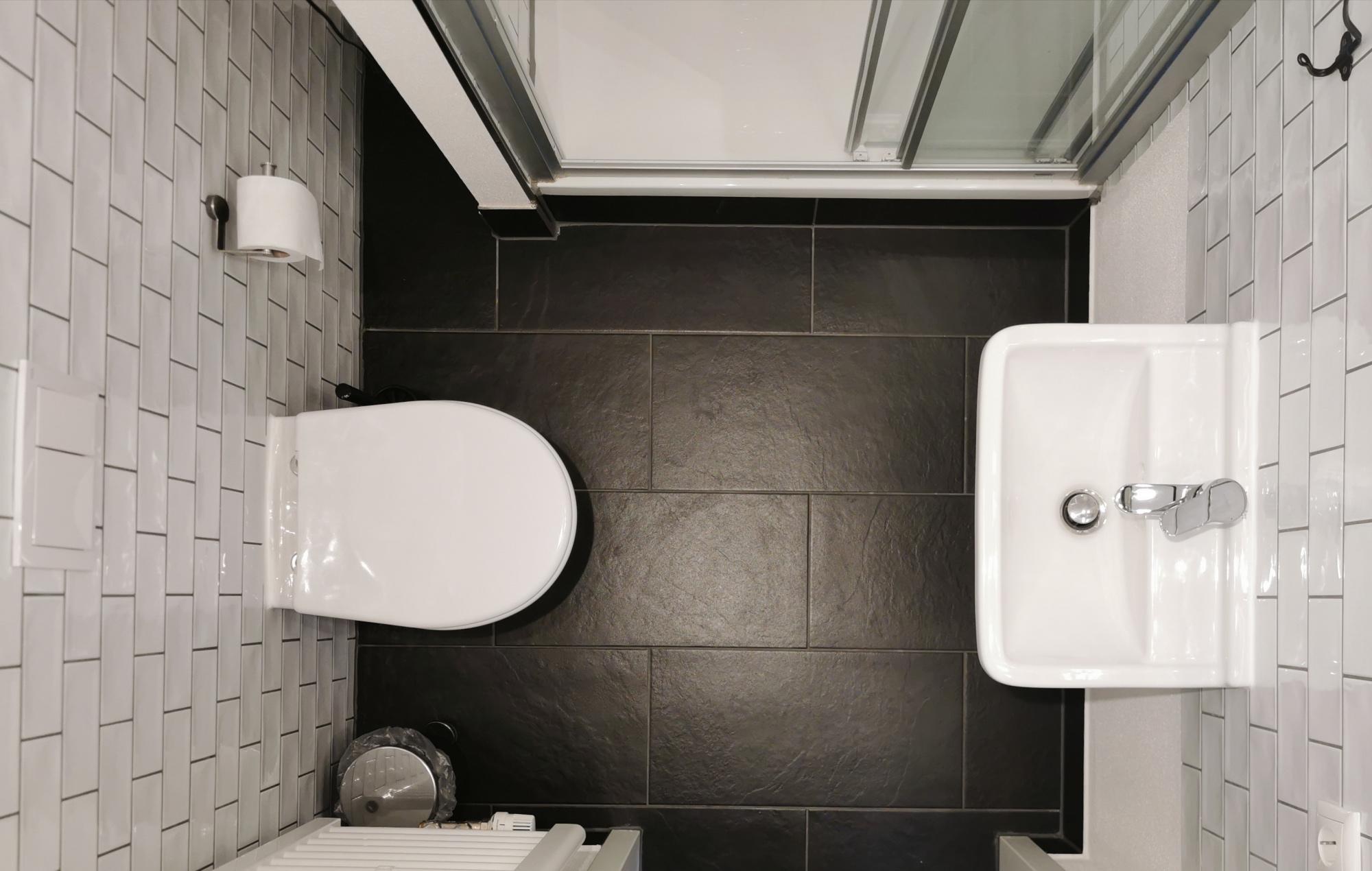 Blick von oben auf eines der hellen Badezimmer mit eleganten schwarzen Fließen.