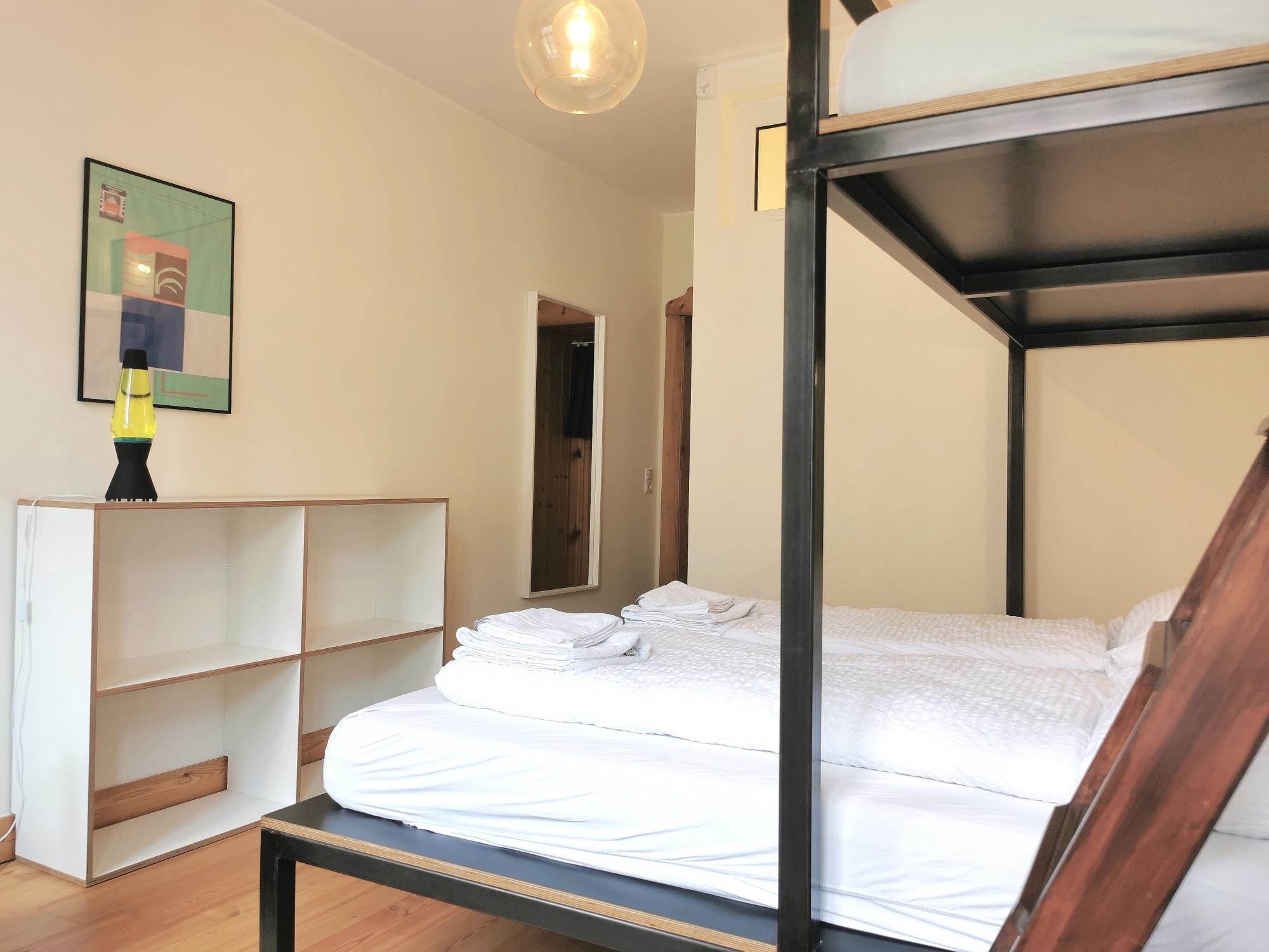 Ein weißes Doppelbett und Regal in einem der neuen Zimmer