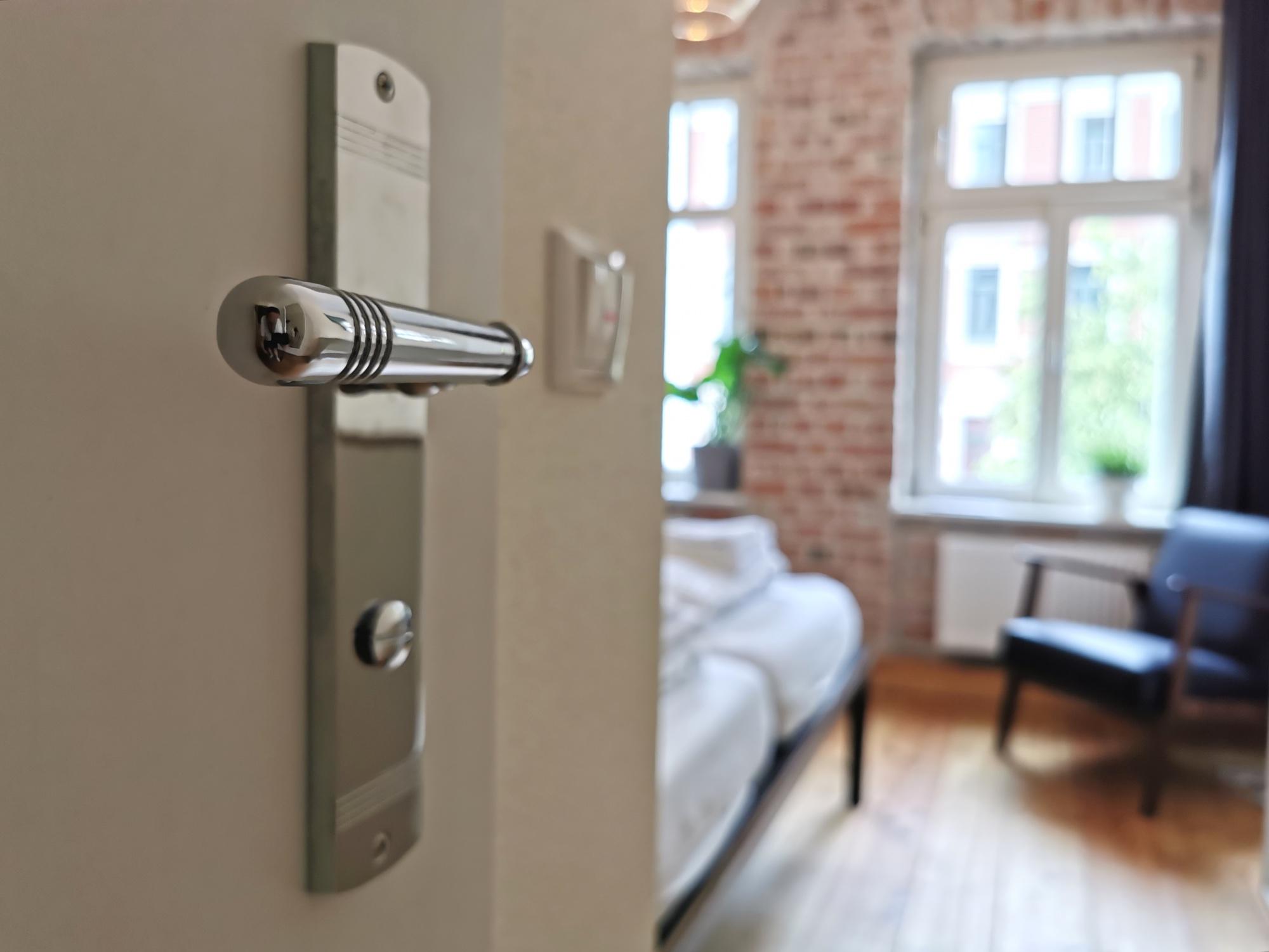 Blick durch die Tür auf eines der schönen hellen Zimmer. Mit einer silbernen Türklinke