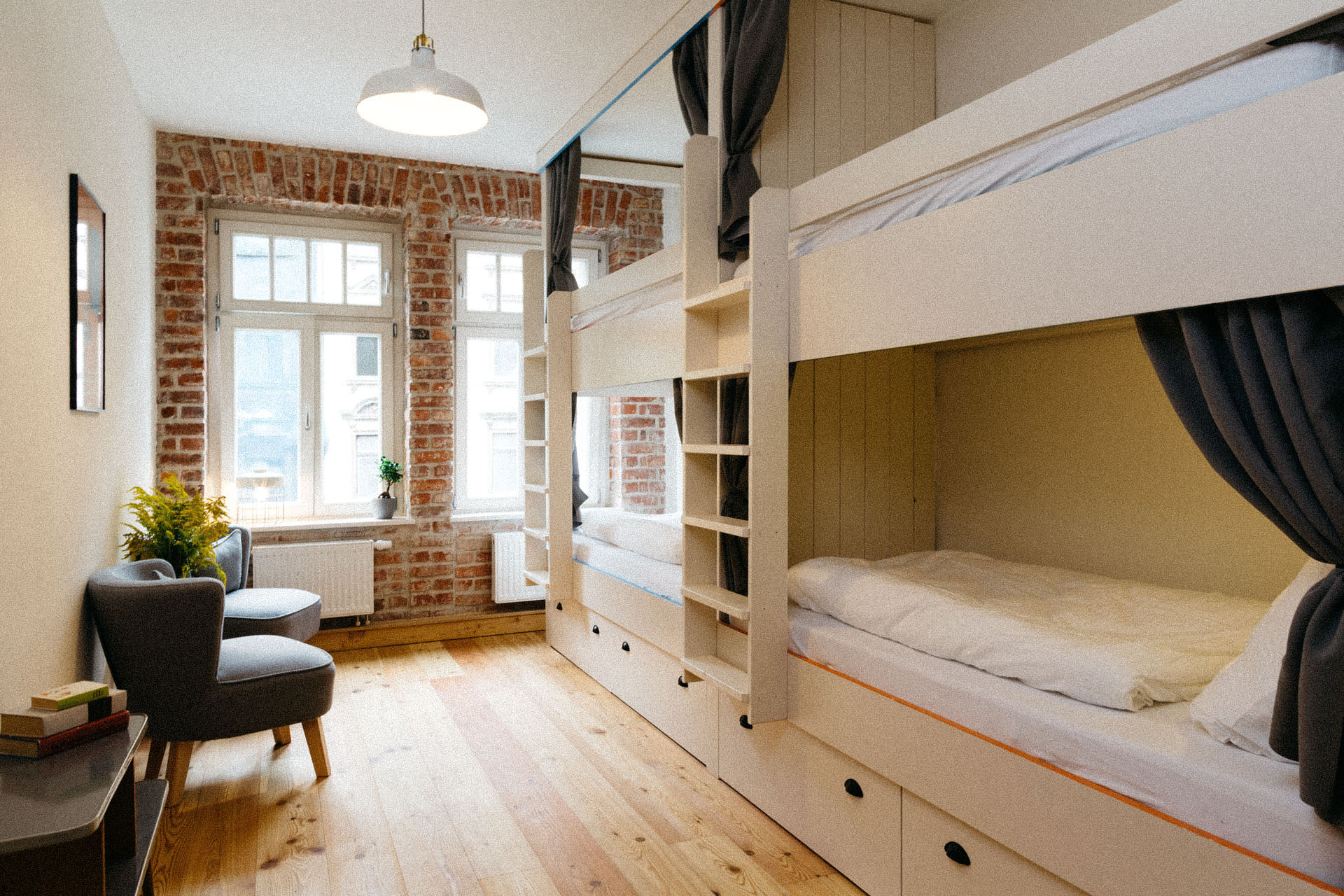 Schönes Zimmer mit 2 Hochbetten und eleganter rustikaler Einrichtung. Die Wände sind aus Backstein. Die Betten sind weiß und mit Verdunklungsvorhängen. Es gibt schöne Sessel und große Fenster