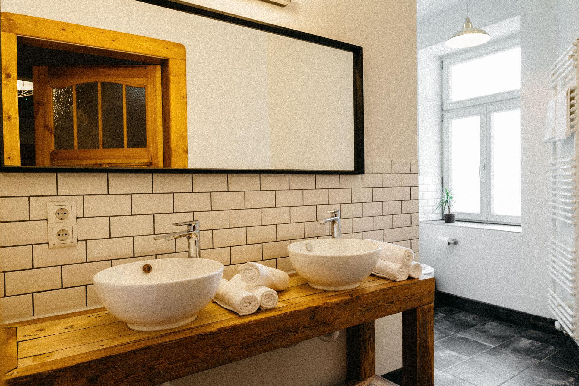 Großer Spiegel mit 2 Schalen als Waschbecken auf einer Holzeinrichtung davor an einer weißen Backsteinwand
