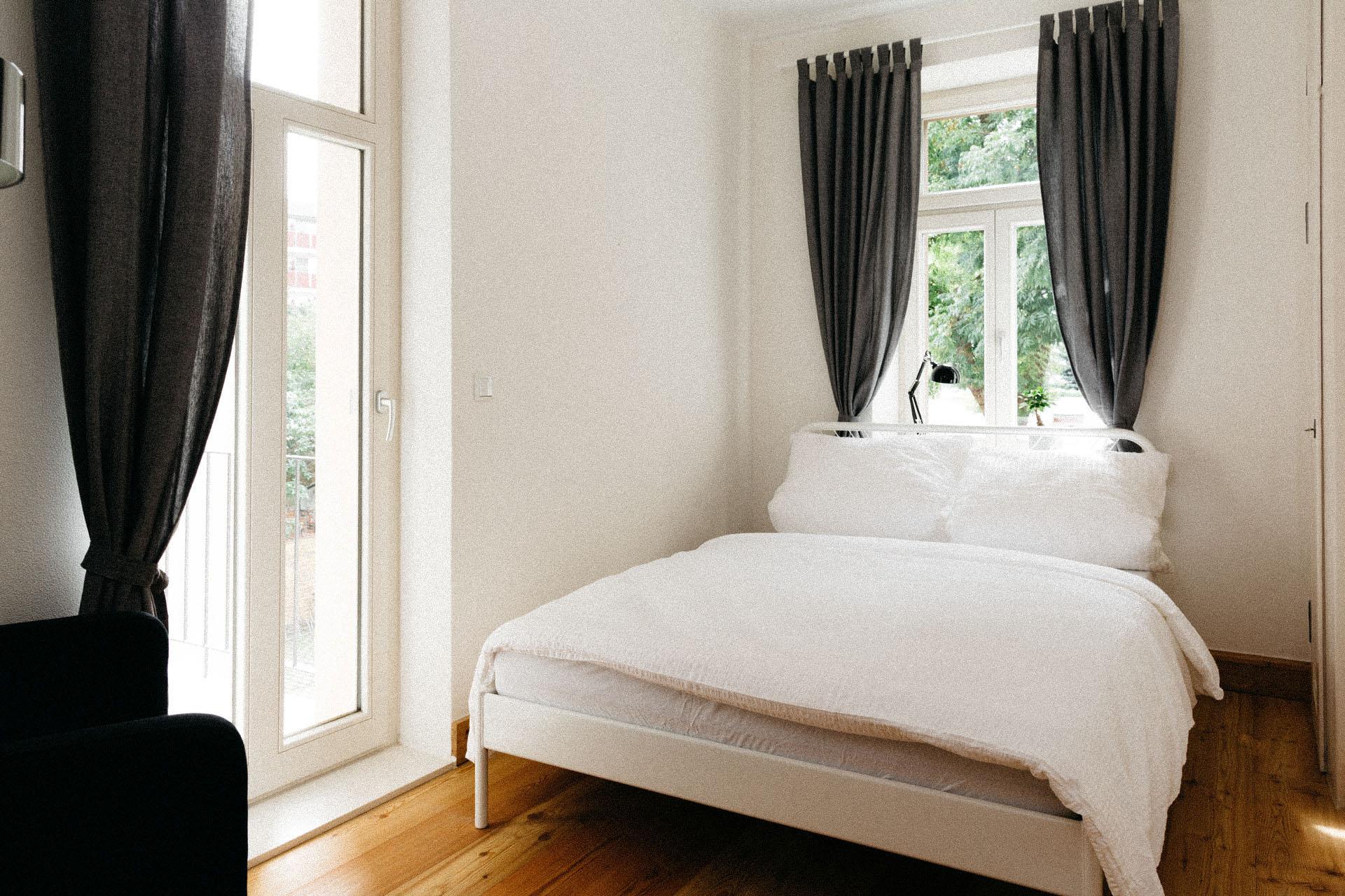 Schönes großes Doppelbett mit dunklen Vorhängen an den Fenstern und einer Tür zur Terrasse links im Bild. Das Zimmer ist sehr hell und freundlich eingerichtet.