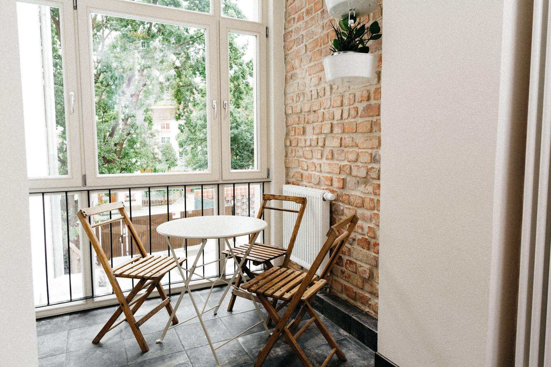 Schöne Terrasse mit schmalen Holzstühlen und großen Fenstern davor