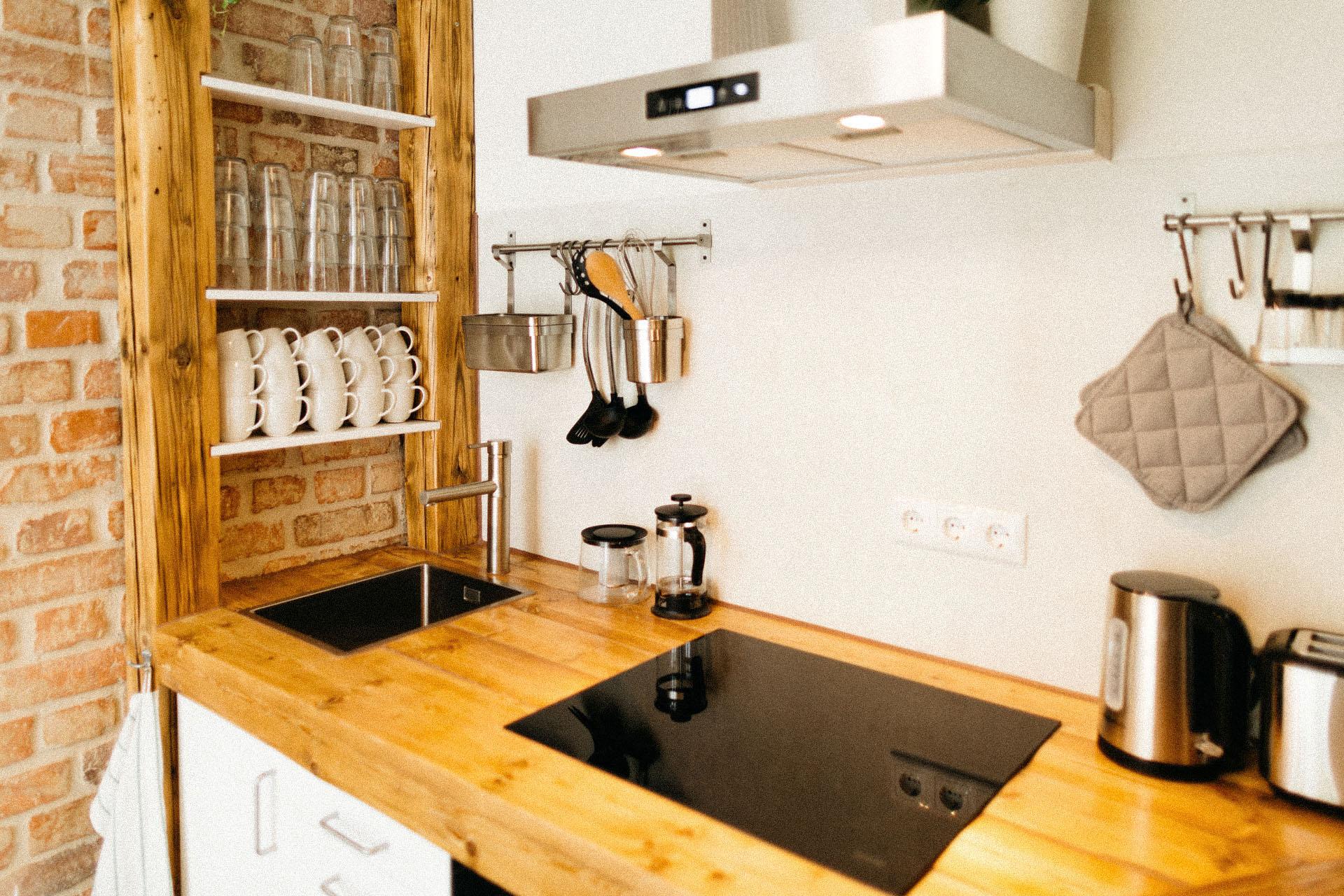 Schöne Holzküche mit Backstein wänden und viel bereitgestelltes Geschirr, einem Herd, und einer großen Spüle