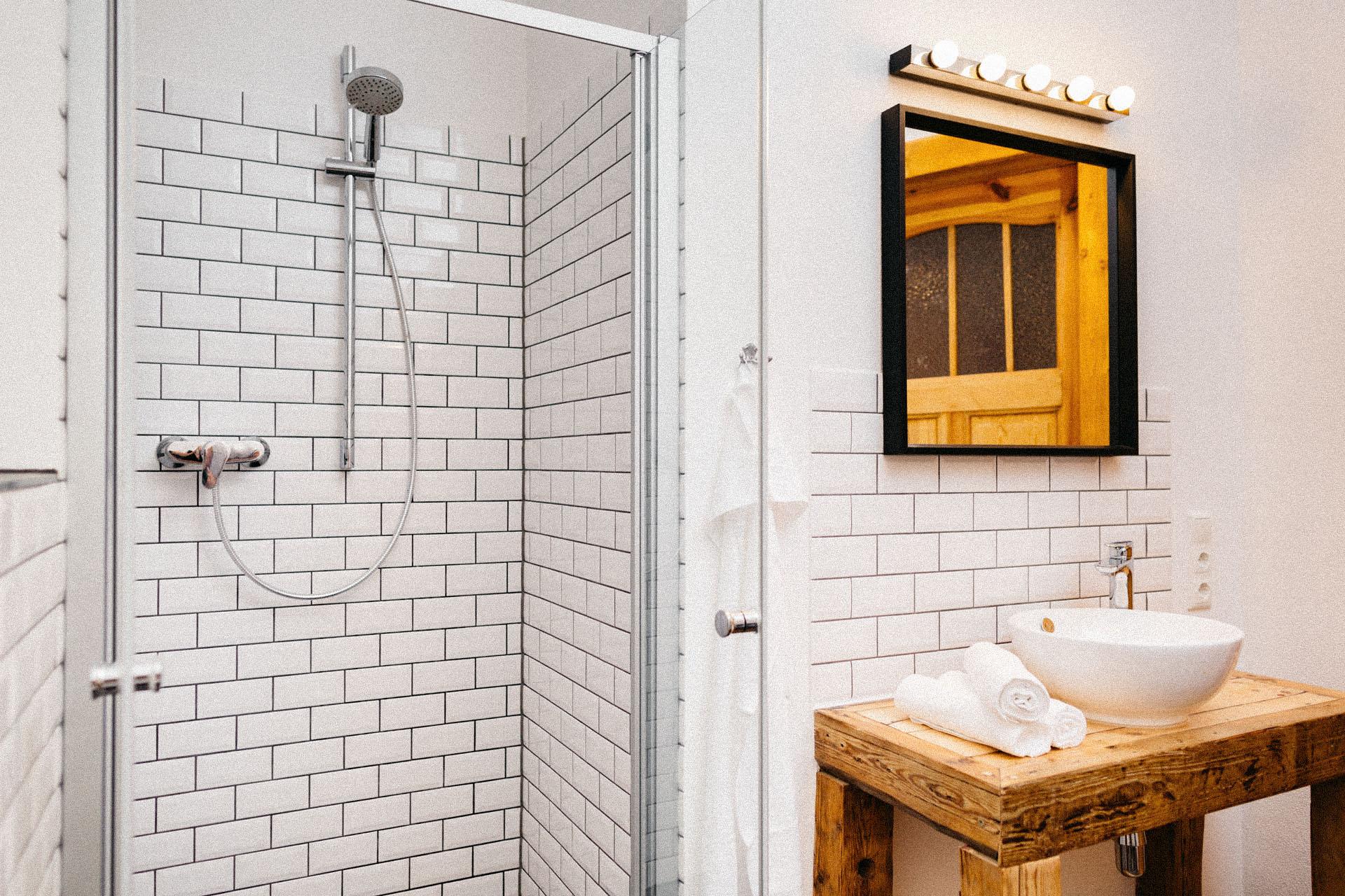 Helle Dusche in einer weißen Backsteinwand eingefasst mit einem großen Spiegel daneben und einem Schicken weißen Waschbecken auf Holz daneben