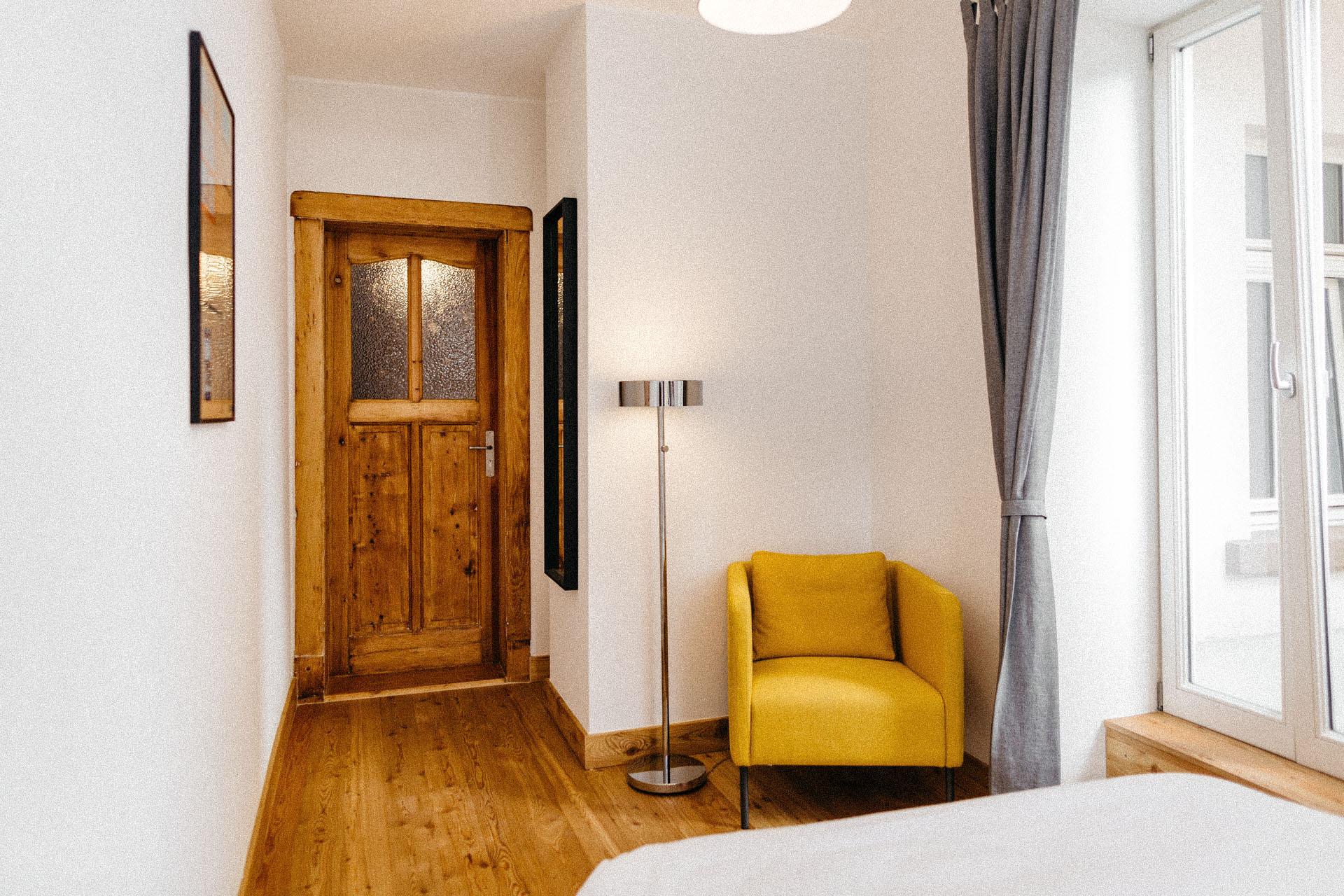 Schöne Holztür im Hintergrund mit einem gelben Sessel rechts neben der Tür und schönem Holzfußboden
